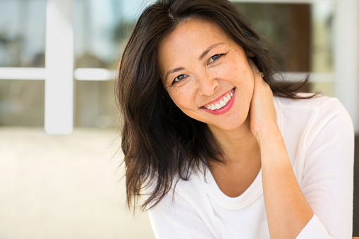 Middle Age Asian Woman Smiling from good visit to Revive Dental and Implant Center